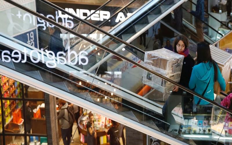 People ride escalators inside a shopping mall in Vina del mar