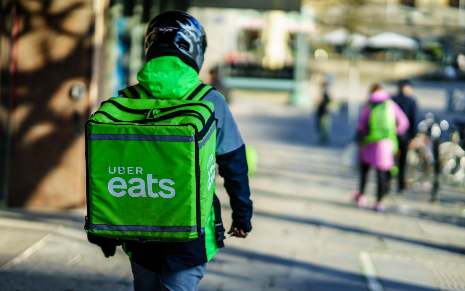 Uber eats delivery person carrying food to people who order by online app